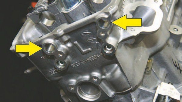 """Coyote's cylinder heads are left (driver) and right (passenger) specific, easily identified by """"L"""" and """"R"""" in addition to respective casting numbers. This is a left-hand 2015 cylinder head as indicated by the """"L."""" Visible here are intake and exhaust cam sensor ports and bolt holes (arrows). Each sensor is cam specific to prevent installation error."""
