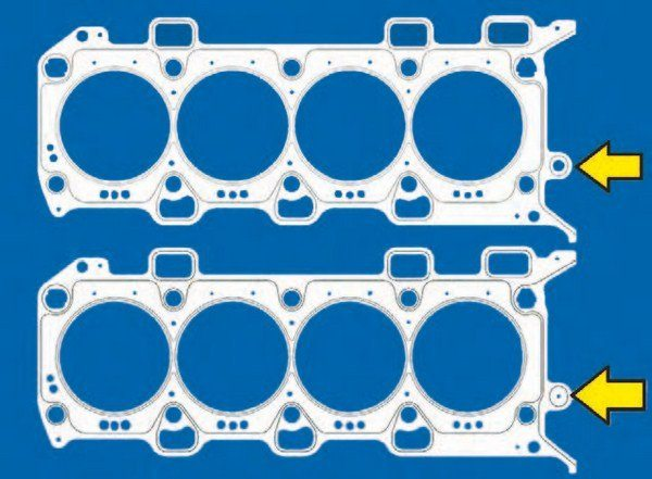The difference between the 2011–2014 and 2015–2016 head gaskets is shown here. On top is the 2015–2016 head gasket with a revised VCV oil galley passage (arrow), which is larger. Bottom is the 2011–2014 gasket with a pinhole-sized galley passage (arrow). (Photo Courtesy Ford Performance Parts)