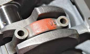 This is the 289 High Performance engine's wider main cap, which is 15/16-inch wide for its entire width and height. Note the orange paint marking, which made it quickly identifiable in the frantic pace of production.