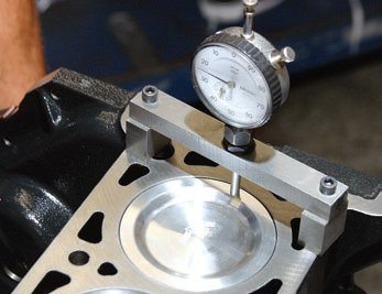 When you infuse more stroke into an engine, you increase compression ratio. This means you need to carefully select pistons and determine cylinder volume, swept volume, compressed head gasket thickness, and piston/deck height. Deck height is being checked here. When you fill the cylinder with more volume, it's vital to know how much, which affects compression. Any time compression exceeds 10.0 to 10.5:1 for a stock, mildperformance build, it's time to choose a piston with a deeper dish or cylinder head with a larger chamber. It usually makes more sense to change pistons.