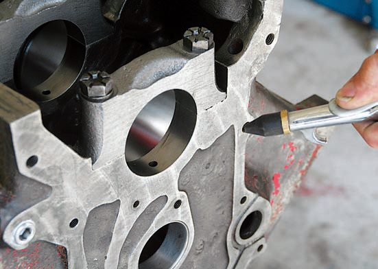 Once the block has been scrubbed clean and rinsed with clean water, use compressed air to blow all the surfaces dry. Coat all these wet surfaces with lubricant because it takes very little time for rust to form. Once dry, coat all machined surfaces of the block, with the exception of the cylinder bores, with either oil or WD-40. Pay particular attention to machined surfaces and bolt holes when drying.