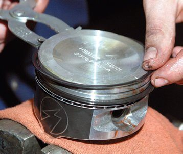 A piston ring expander is used for ring installation. Never roll piston rings on. Rolling them on distorts them and prevents proper seating.