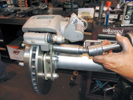 The Currie disc conversion kit uses an OEM/Ford caliper and rotor from a late-model Thunderbird. This makes replacement pads very easy to find. The caliper is very low in profile and fits inside 14- and 15-inch wheels. The axles must come out to install the main mounting plate (new axle seals are included) but the rest of the mounting brackets are simple bolt-ons once this is done. This kit uses a single-piston sliding caliper over a vented rotor, which is fine for daily-driver and mild strip/track use.