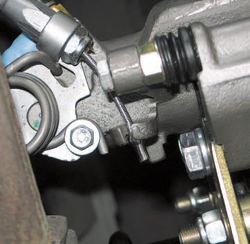 When converting from drums to discs, or even when upgrading discs already on the vehicle, you often have to make some kind of adaptation for the parking brake cables. This is a cable style where the end of the cable has a metal ball that engages a cast-in cup with an access slot. The body of the cable passes through a hole in another cast tab.