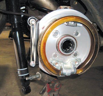 "This style of parking brake is an internal drum design. Ironically, one area where drum brakes are often superior to discs is as a parking brake. This is due to the drum's larger working area, thus requiring less pressure from the pedal or lever to actuate so you don't have to be a bodybuilder to stop the car from rolling down a hill, for example. You still have a disc brake to do the main stopping work but the small, internal drum does a better job as a parking brake. A unique rotor is required because the drum is part of the rotor ""hat"" design."