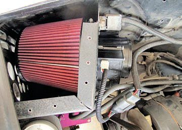 When a MAFS-based EFI system is used, all the intake air must go through the sensor so only a single duct can be used. The duct size can be fairly large as long as the sensor is matched to it. This is a ram air setup on a 1965 fastback 347 stroker equipped with an EEC-IV. Placing the filter inside a box behind the grille ensures a good supply of cool, pressurized outside air. The larger (97 mm) Abaco/DBX digitally programmable sensor sits right behind the filter on the other side of the box. The sensor has a very large and smooth bell-shaped opening to aid flow into it, plus the straight ducting behind helps ensure accuracy.