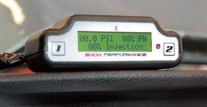 The LCD display mounts with Velcro strips, usually on top of the dash, in the driver's line of sight. The display shows boost pressure, fuel injector pulsewidth, and the percent of maximum flow at any given time. The parameters for the mapping are all quickly and easily programmed from the driver's seat using two buttons (shown). A mixture flow gauge is also available for standard gauge pods.