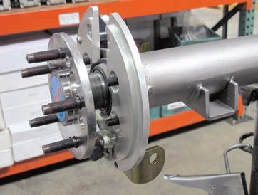 The drum-in-hat system may require the removal of the axles to mount the billet backing plate. The clearance between the axle flange/wheel studs, the backing plate, and its studs must be checked against the spec provided by Baer to make sure it is enough to avoid any problem with contact. The larger hole in the axle flange allows access to the backing plate nuts so they can be tightened.