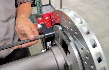 As with the front fixed calipers, these at the rear also require shims to ensure the calipers are properly centered over the rotors. Here, a shim has been placed between the black caliper mount and the aluminum parking brake backing plate. Care must be taken to ensure the gap on both sides of the rotor is equal and uniform.