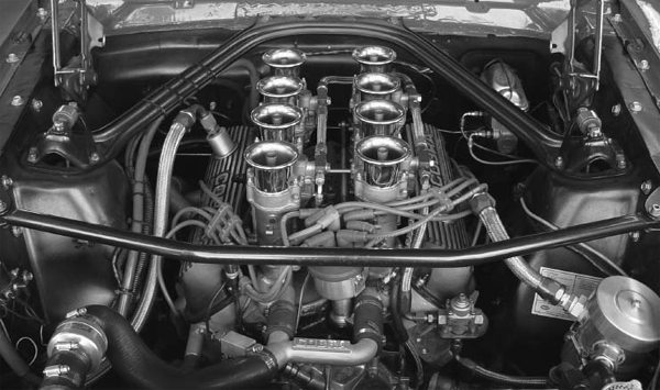 The Export brace ties the shock towers to an integral section of the firewall. This Mustang has a factory Export brace. The bar that runs in front of the engine between the shock towers is called a Monte Carlo bar. This bar is not a factory piece.