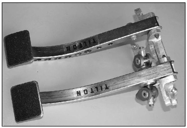 This is a two-piece, fixed-caliper design. Two separate machined blocks are bolted together. This caliper requires an external balance tube to balance the left and right half of the caliper's fluid pressure.