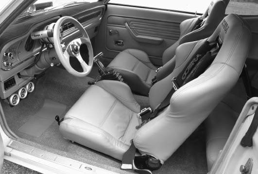 The Cobra Daytona front and rear seats were covered in leather by Katzkins to match the original interior and Auto Custom Carpet. The addition of AutoMeter gauges, B&M shifter, and Dino wheel round out the interior. (Photo courtesy Phil Royle)
