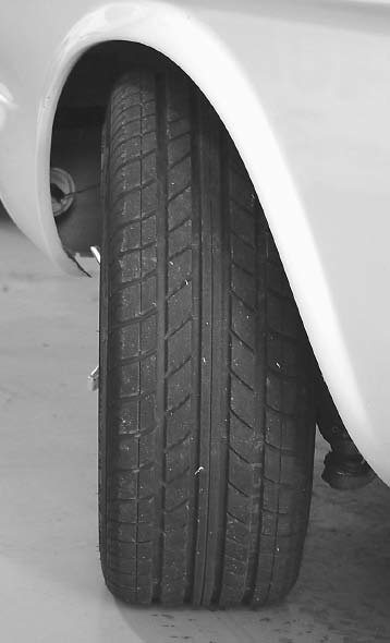 This front tire is exhibiting slight negative camber. The top of the tire is tilted slightly inward. This car corners well. The entire width of the tire tread is able to get traction on the ground. It's possible a little more camber would increase cornering performance.