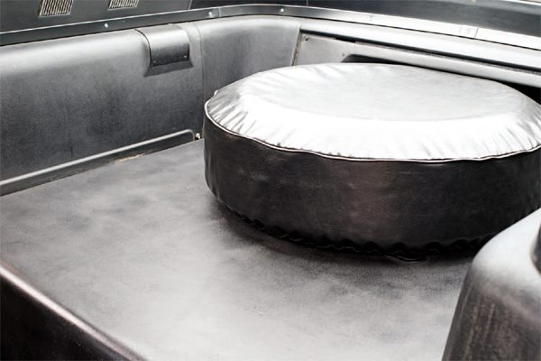 The SCCA said the Mustang GT350 had to be a two-seater, and Shelby American complied: the spare tire was mounted atop a plastic shelf that replaced the Mustang's folding rear seat and also the trap door between the rear seat and the trunk. The rear seat catch was deleted and covered with a simple trim piece of textured aluminum on some cars but plastic on others. The movement of the spare tire out of the trunk gave 1965 Shelby owners the most unrestricted trunk space of any year Shelby Mustang.