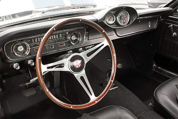 Wood steering wheels came in three basic types: 16-inch diameter (supplied by Derrington) with a chrome hub and slotted spokes, which was the same steering wheel as used in the Cobra; 15-inch diameter with aluminum hub and holes in the spokes; and 15-inch diameter with an aluminum hub and slotted spokes (both supplied by Moto-Lita). The change in diameter from 16 to 15 inches was made to provide better steering wheelto-thigh clearance for the driver and the change from holed to slotted spokes was a result of what Moto-Lita offered at the time. Like the wheel, the center cap ornament was the same as was used on the two-seat Cobra roadster; the GT350 emblem had not been thought of yet.