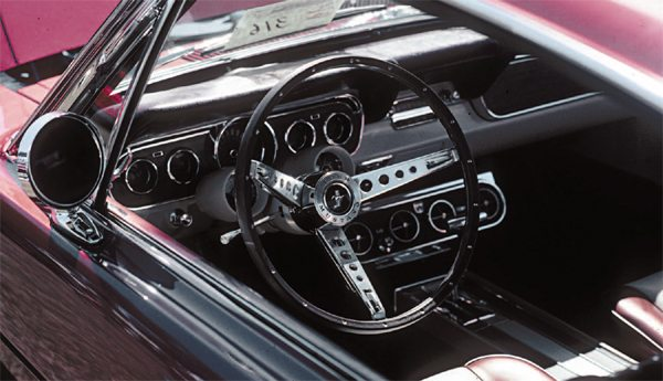 "In the absence of a suitable wood steering wheel—one of good, consistent quality with an integral center horn button—Shelby American found a substitute almost literally under their noses: the Ford Mustang simulated wood wheel that accompanied the interior décor option, the so-called Mustang ""pony"" interior, filled the bill. Shelby-bound Mustangs could have the fancy tiller installed on the San Jose assembly line, saving Shelby American the hassle of swapping wheels at LAX."
