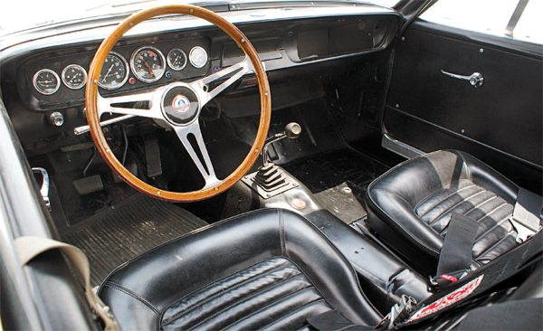 As devoid of creature comforts as the street GT350's cockpit was, the R-Model's was even more so. All carpeting, seam sealing, and sound deadening material was deleted at San Jose, as were the welded-on dash supports to attach the Mustang/GT350 padded dash. The heater was also deleted, as was the heavy cast-metal glove compartment door, although the cardboard glove box liner was retained. Floors were painted semigloss black and the R-Models got the same wood Derrington or Moto-Lita steering wheels as their street brethren.