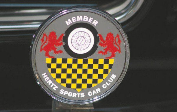 """The Hertz Sports Car Club was formed in 1958 to allow traveling business executives the opportunity to rent a fun vehicle while on an otherwise-boring business trip. The Club's logo featured lions, checkerboard, and a wire sports car wheel. The emblem was made into grille badges and given to renters who became members of the Club. Accompanying the badge were other """"goodies"""" such as tote bags, garment bags, playing cards, and drinking glasses"""
