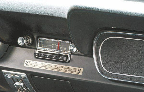 """Part of the solution to the GT350H's hard brake pedal feel was a decal warning renters of the GT350H's hard brake pedal feel. Done on gold foil with black lettering (as you would expect), the decal admonished that """"this vehicle is equipped with competition brakes"""" and that """"harder than normal brake pedal pressure may be required."""" The placement of the decal varied with some cars having the decal applied to the padded dash above the radio and some to the metal dash below. Radios were dealer-installed as mechanics from Hi-Performance Motors (Shelby's retail outlet and shop) performed the installation on all 1,000 Hertz cars (plus a handful of non-Hertz GT350s). """"Deluxe"""" lettering on some radios was once thought to be unique to Hertz cars when in fact it was a random occurrence, an artifact of one of Ford's several radio suppliers using that lettering on the faceplates of its products."""