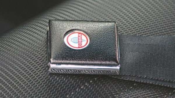 To reduce costs, the Shelby Mustang for 1967 utilized the standard 2-inch-wide Ford lap belts (in place of the costlier 3-inch competition seat belts of the 1965 and 1966 cars). Differentiation from the basic Mustang was via a small COBRA decal on the release button. Early cars had seat upholstery with smooth inserts while later cars incorporated Comfort Weave vinyl in the seat centers.