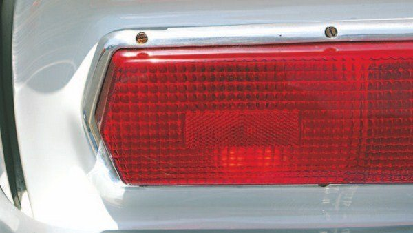 Further variations were seen in mounting the taillight bezel and lens to the tail panel with the early variations mounting the bezel flush to the tail panel surface (known as the flat tail panel; left). The later tail panels mounted the bezel and lens to a raised area. This style is often referred to as the raised tail panel (middle). This provided additional space in the trunk as it shifted the inner taillight box farther back. Some cars utilized aluminum trim bezels with exposed mounting-screws, while others lacked the external screws. Externally-screwed bezels were used on both flat and raised tail panels (right).
