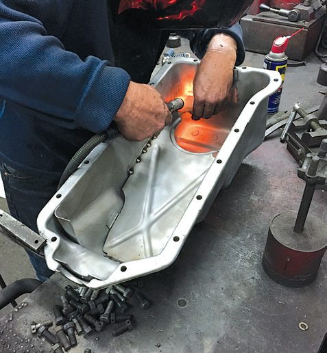 After everything is thoroughly cleaned, blasted, and cleaned again, the baffl e is welded back into position. Careful positioning is necessary because the oil pickup sits in the circular groove toward the rear.