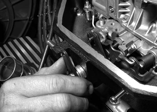 23. Prior to installing the clamshell top of the air box, the carburetor throttle linkage is hooked up and tested. The lid is then permanently bolted on.
