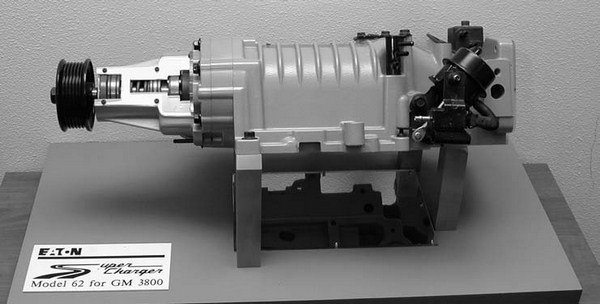 "A cutaway of a 3800 Series Eaton/Magnuson supercharger shows the electrical solenoid- activated bypass actuator, which is used to ""burp"" the supercharger in-between gear changes. This is done so that it takes some of the power pit of the car's transmission to soften up the shifting."