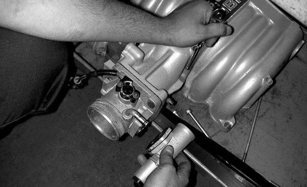 7. Off comes the 5.0L Idle Air Control (IAC) motor from the factory Ford throttle body, which is then reinstalled onto the polished Accufab 70-mm throttle body using the factory 5⁄16-inch throttle body mounting bolts.