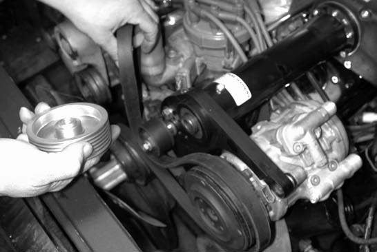17. Next comes installing the serpentine blower belt. Installation is made easier by first removing the upper pulley.