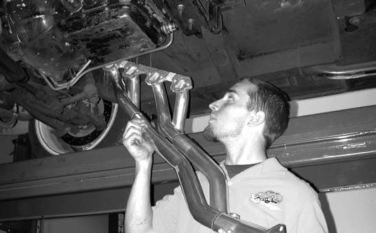 24. After removing the old exhaust system, the passenger-side headers are installed from down below. Note that the gaskets have already been placed on the header flange using Permatex and masking tape; this eases installation.