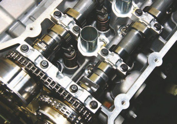 On top is a look at the complete valvetrain system. Before you are the intake and exhaust cams, which ride in pressurized journals on an oil wedge. Beneath the cams are finger-style roller rocker arms, which are positioned on top of lash adjusters.