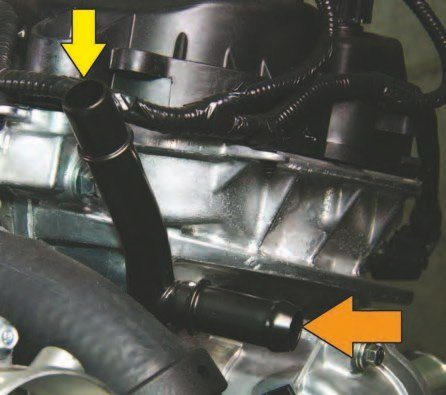 """Heater hosepipe connections are incorporated into the cylinder heads in front as shown here. This is the left-hand (driver) side with the cockeyed """"Y""""-pipe. The top pipe at 12 o'clock (yellow arrow) is coolant flow from the heater hose. The lower pipe (orange arrow) is from the coolant expansion tank at the radiator. When you add coolant, it flows from the tank to this inlet pipe."""